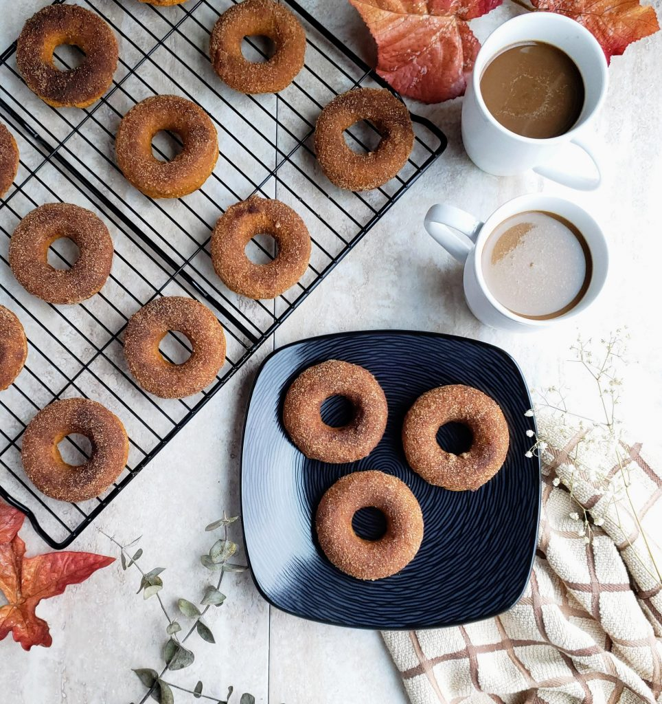 A black plate with three baked pumpkin donuts on it next to a wire rack full of donuts and two white mugs of coffee