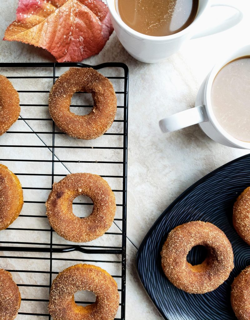 black plate with healthy baked pumpkin donuts next to two white mugs of coffee and a wire rack full of donuts