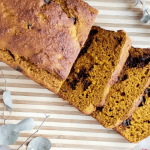 slices of healthy chocolate chip pumpkin bread on a striped cutting board