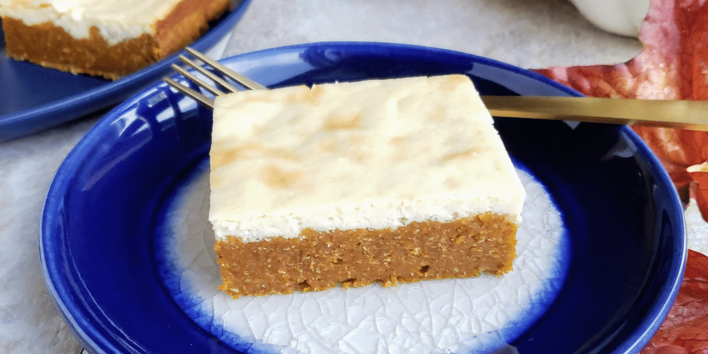 single slice of healthy pumpkin cheesecake bar on a blue plate