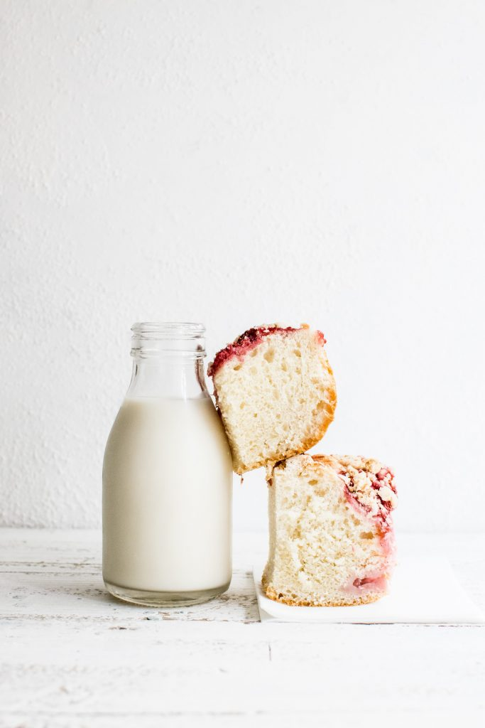 bottle of milk with two large slices of fruit cake stacked next to it