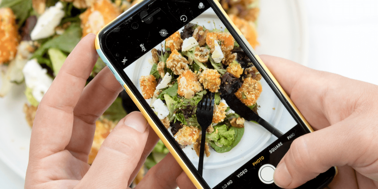person taking a picture of their meal with their phone