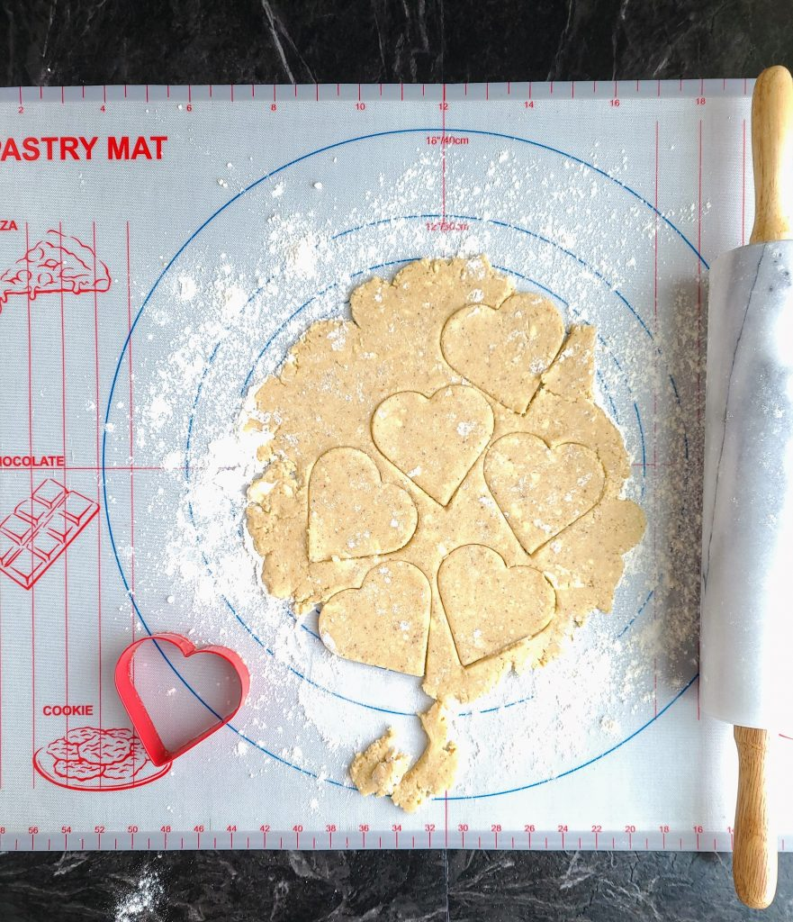 gluten free sugar cookie dough rolled out and cut out with heart shaped cookie cutter
