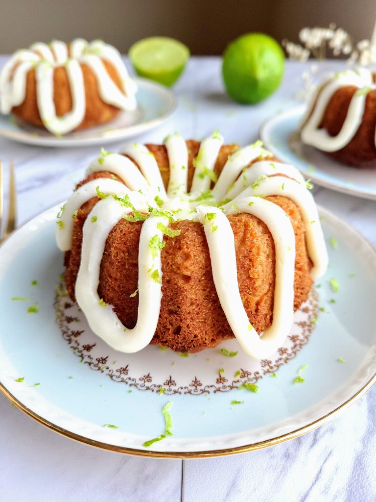 healthy coconut lime cake on a light blue plate with two cakes and limes in the background