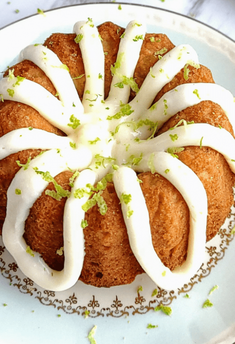 healthy coconut lime cake with two cut limes to the right and a gold fork to the left