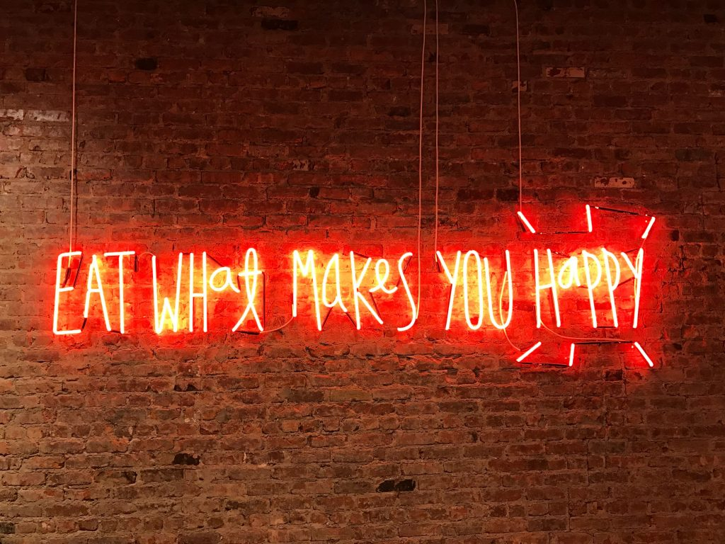 "neon sign that says ""eat what makes you happy"""
