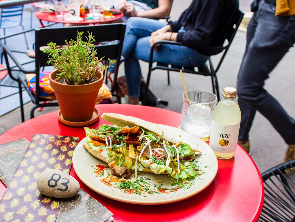 outdoor red restaurant table with a meal of tacos and juice on top
