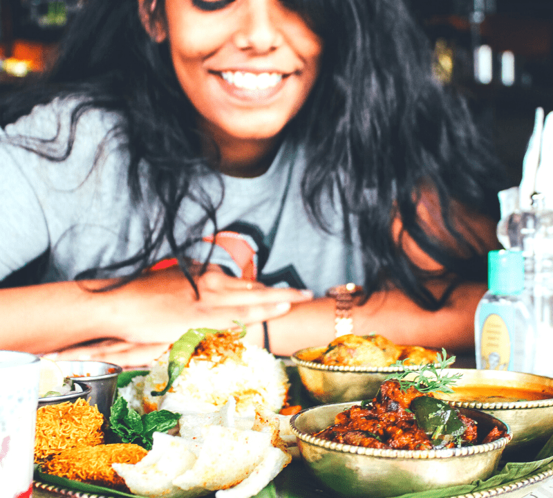 woman sitting at a restaurant table looking at Chinese food