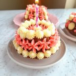 healthy gluten free smash cake with a burning candle sticking out the top