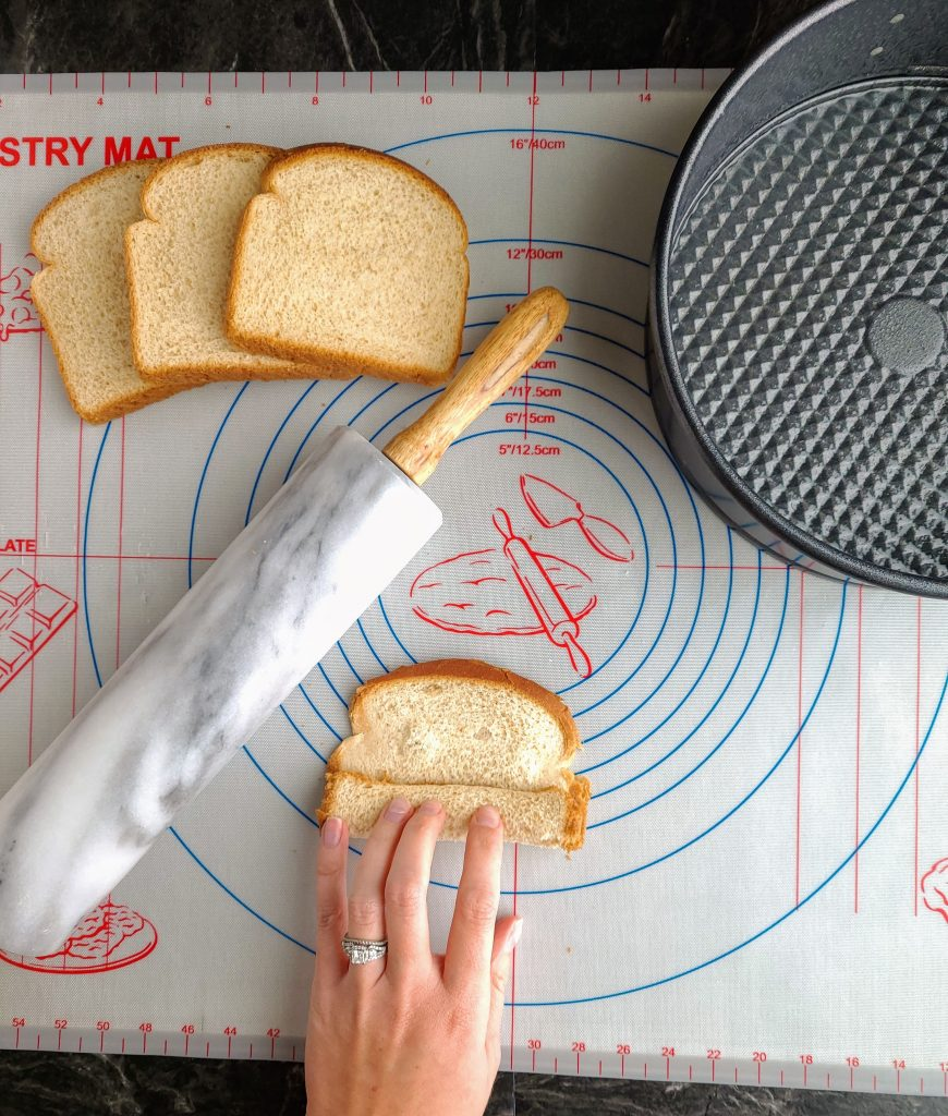 slices of bread, a rolling pin and springform pan with a hand rolling some bread
