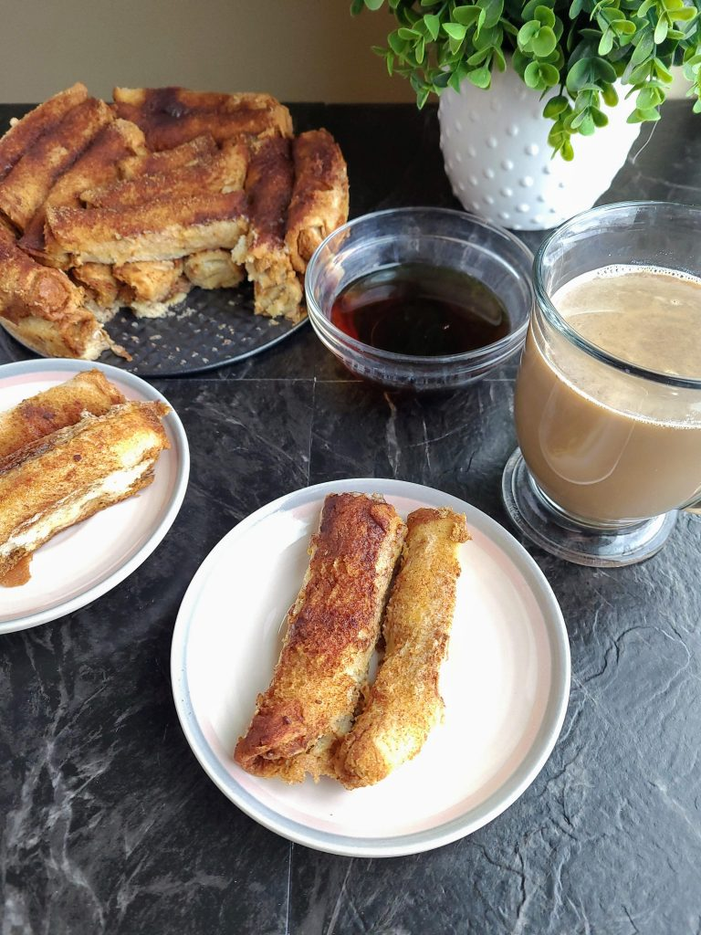 French toast roll ups on a white plate with a coffee cup, small bowl of syrup and green plant in a white vase