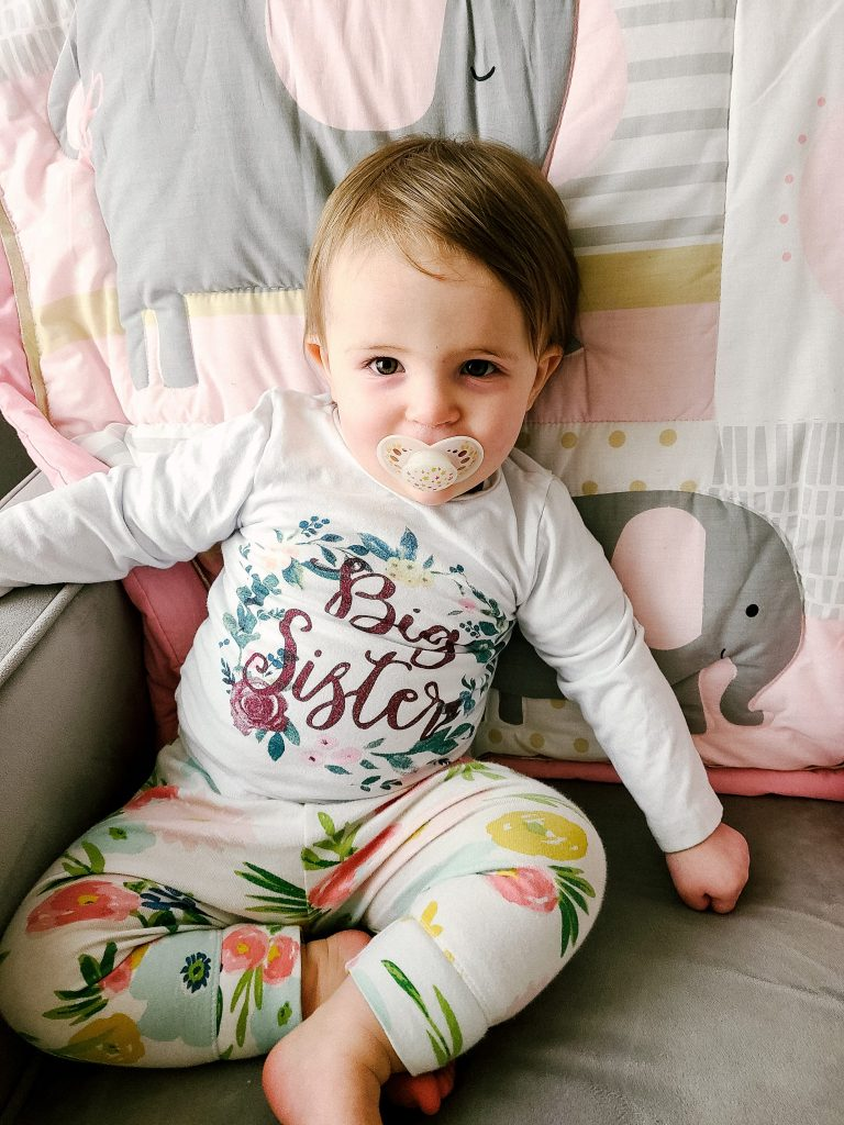baby with a binkie sitting in a rocking chair with a big sister shirt on