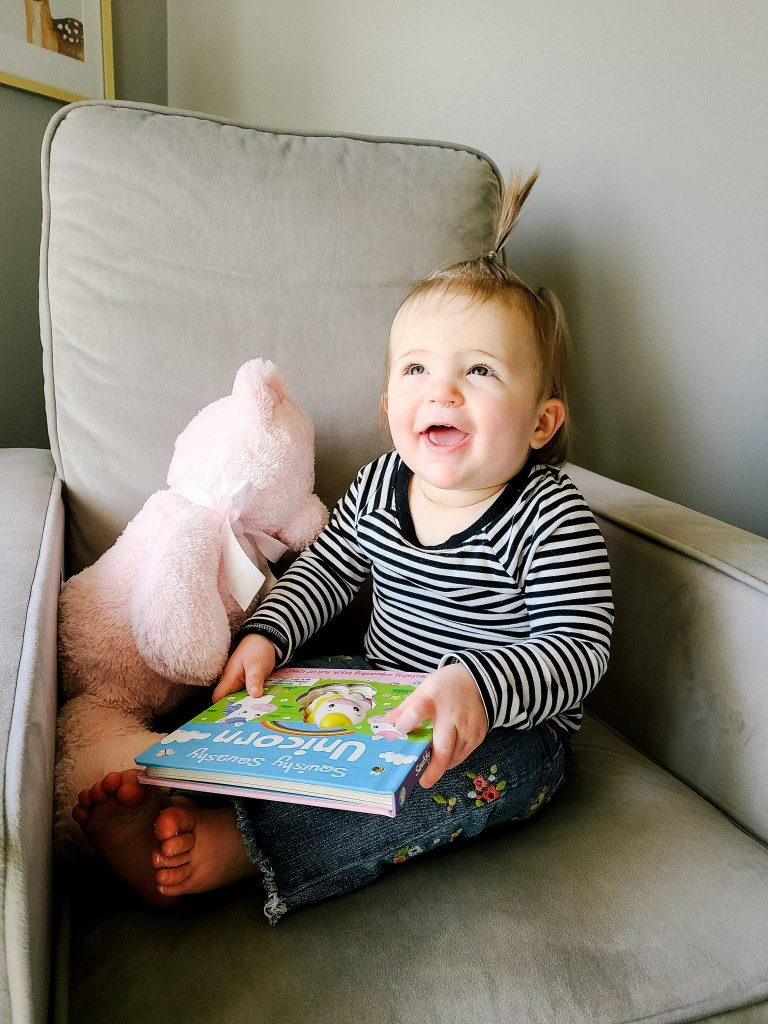 baby sitting in a rocking chair smiling and holding a book with a pink teddy bear next to her