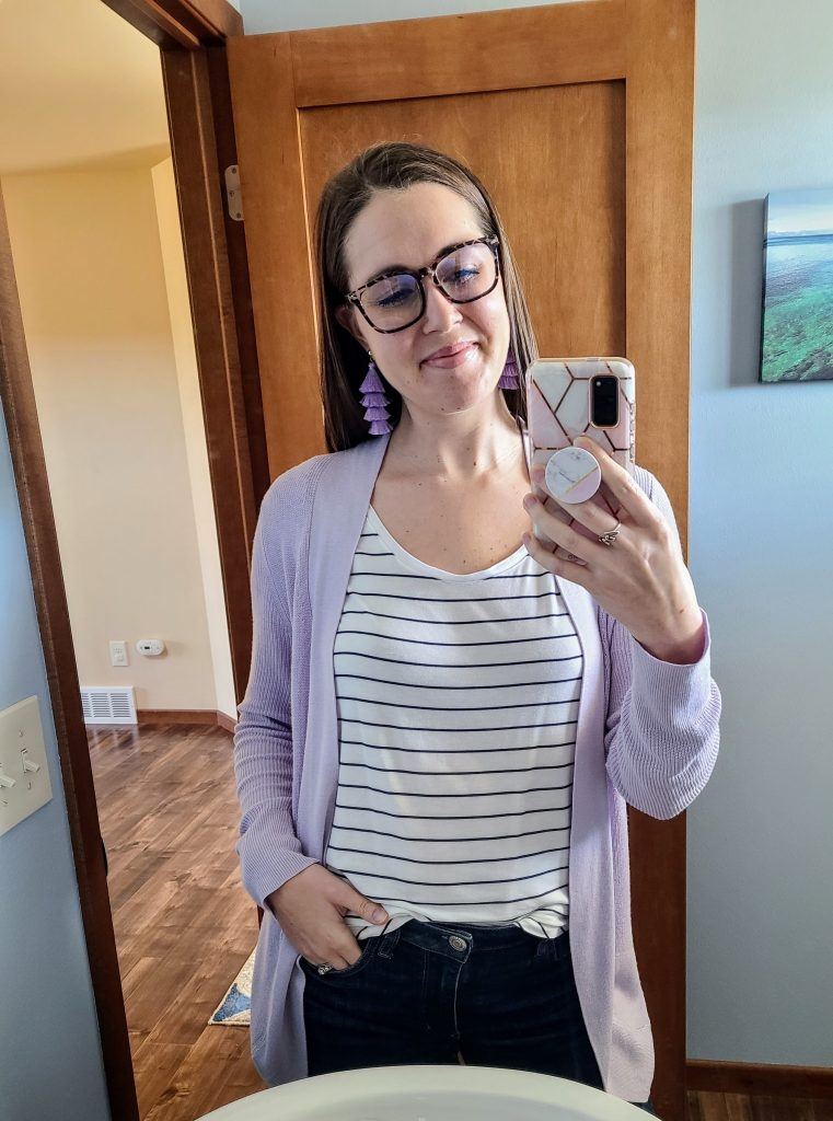 woman with glasses and purple tassel earrings taking a selfie in a mirror
