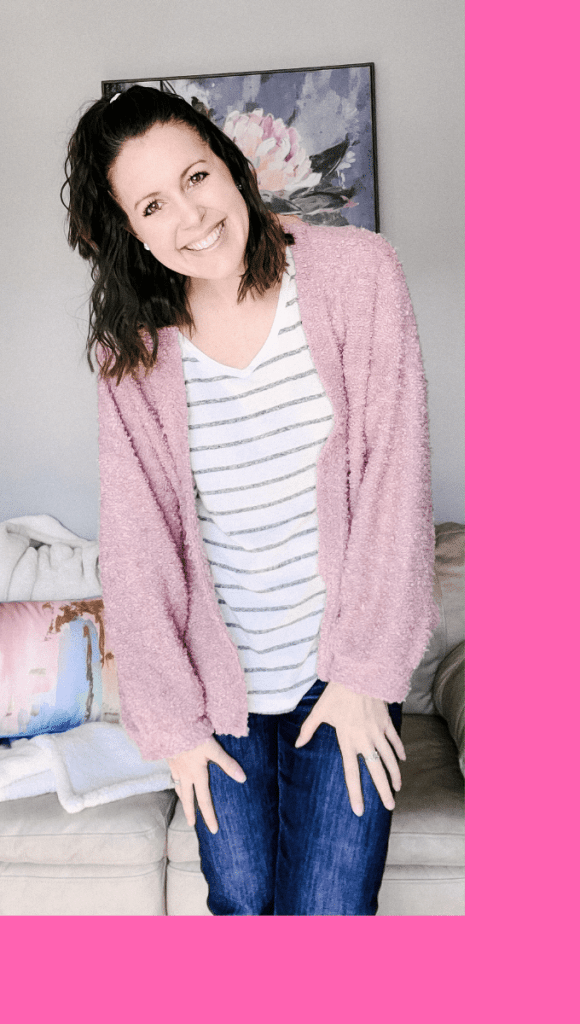 woman with a striped shirt and pink sweater smiling at the camera