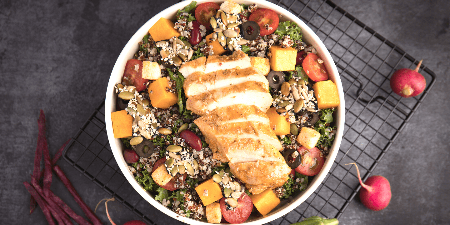 loaded salad bowl with sliced baked chicken on top
