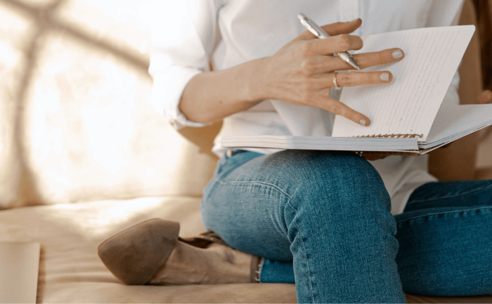 woman sitting on a couch opening a journal